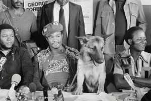 """11 Sep 1974, Paris, France --- Original caption: 9/11/1974-Paris, France- Heavyweight champion George Foreman, accompanied by his dog, """"Dago,"""" answers newsmen's questions during a stopover at Orly Airport 9/11. Foreman is enroute for Kinshasa, Zaire, where he will defend his title, 9/25 against Muhammad Ali. """"Dago"""" is shown looking at the camera. --- Image by © Bettmann/CORBIS"""